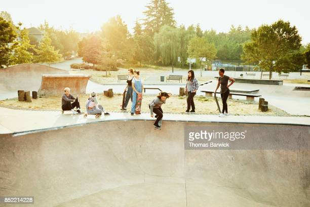 Female skateboarders skating together in skate park on summer morning