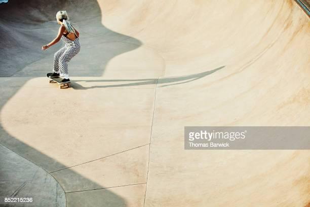 Female skater in bowl in skate park on summer morning