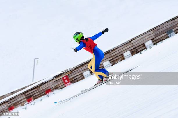 female ski jumper practicing telemark landing, - telemark stock pictures, royalty-free photos & images