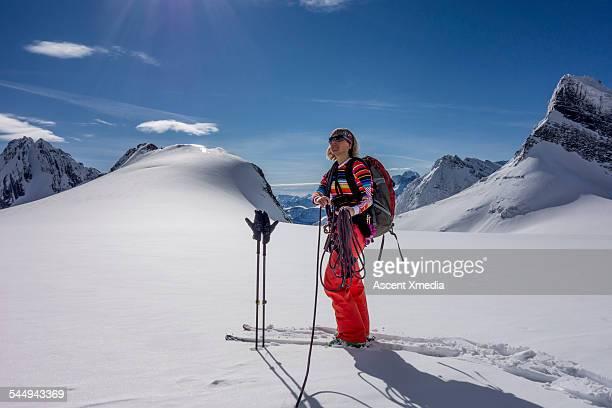 Female ski mountaineer pauses, high mountain crest