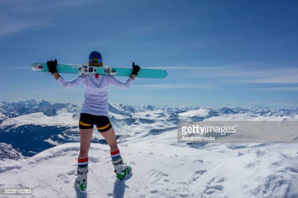 female ski mountaineer stands on summit, looks off - korte broek stockfoto's en -beelden