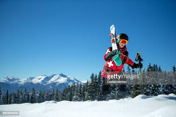 Female ski patrol walking through deep snow.