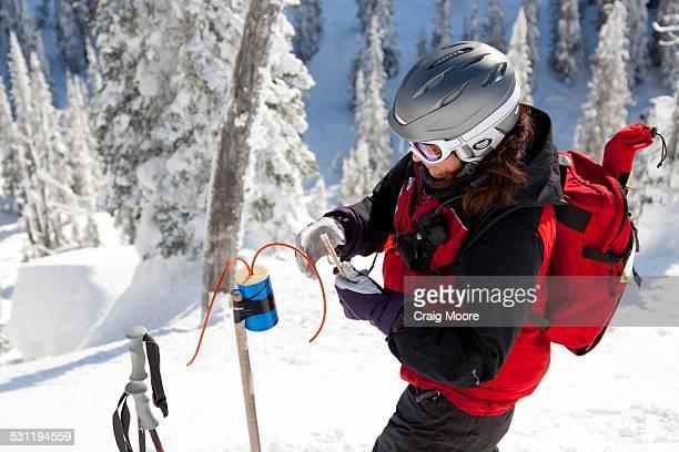 A female ski patroller prepares an explosive.