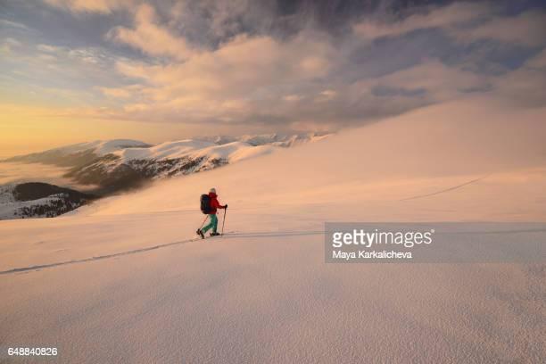 Female ski tourer walking on a mountain ridge at sunset