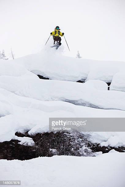 A female skier jumping off a cliff on a stormy day in Colorado.