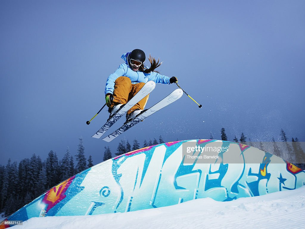 Female skier jumping in mid-air over a rainbow box