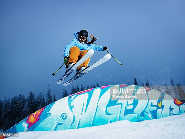 Female skier jumping over a rainbow box