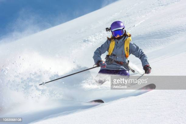 female skier skiing on fresh snow - downhill skiing stock pictures, royalty-free photos & images