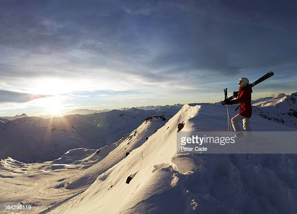Female skier stood at top of slope admiring view