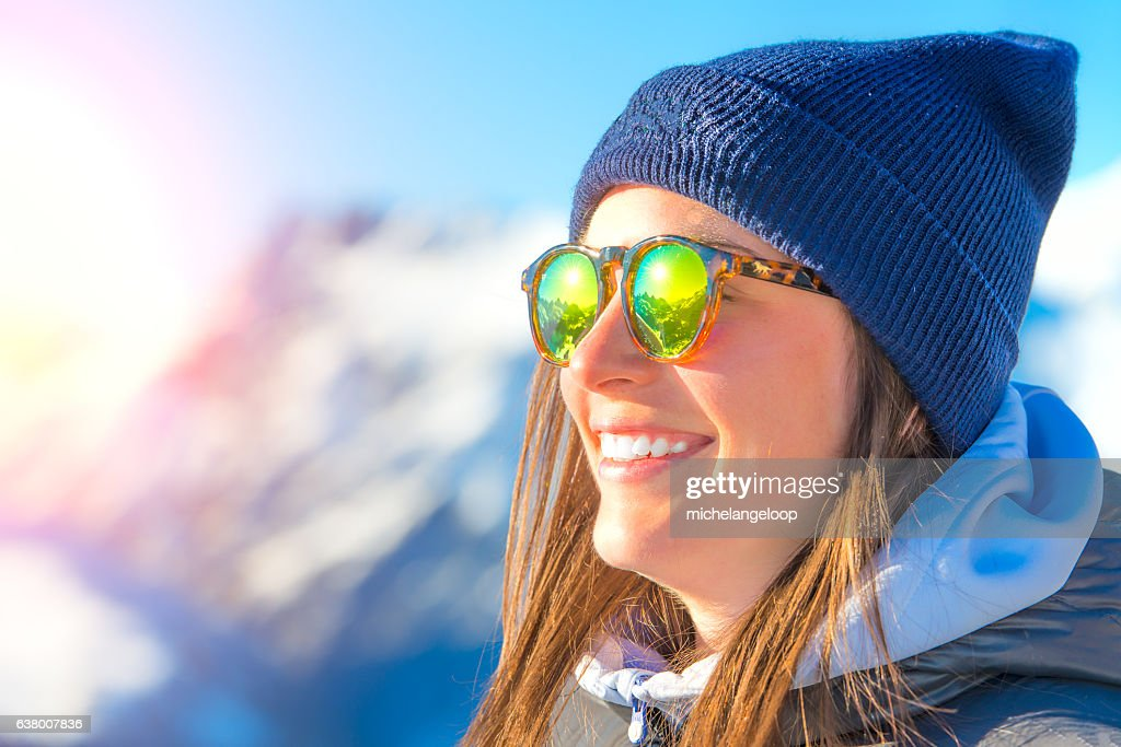 Female skier with skis smiling and wearing ski glasses : Stock Photo