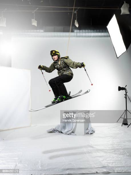 Female skiier in the air in a studio