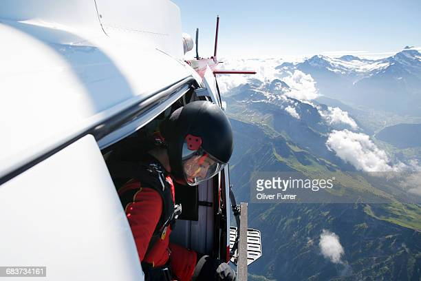 Female sky diver in helicopter checking for exit over mountain, Interlaken, Berne, Switzerland