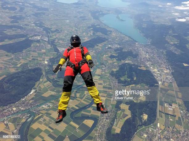 Female skydiver free falling on back above landscape