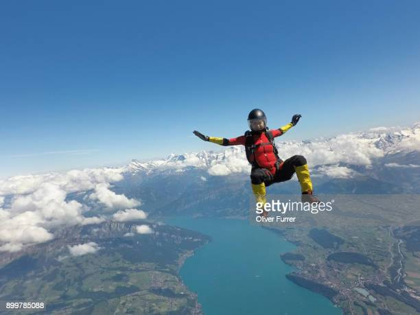 female skydiver sitting up in free fall above clouds and lake - skydiving stock photos and pictures