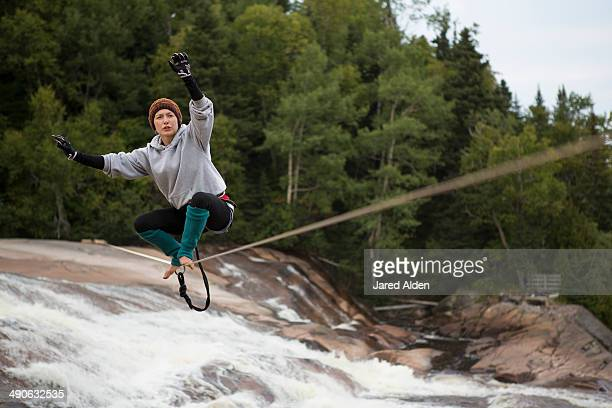 Female slackliner standing up on a slackline that spans a river