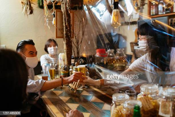female small bar owner giving beer to customer from behind protective clear plastic curtain - catering building stock pictures, royalty-free photos & images
