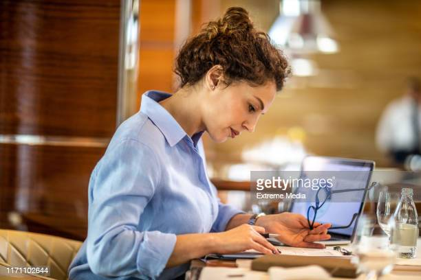 female small business owner making a financial report of her company from a pie chart on his laptop while sitting in an exclusive restaurant - bureaucracy stock pictures, royalty-free photos & images