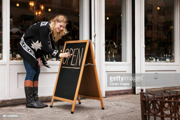 female small business owner making open sign outside wine shop - open for business stock pictures, royalty-free photos & images
