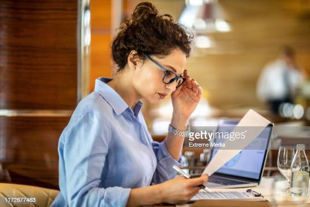 female small business owner reading a paper document while sitting in a restaurant - financial analyst stock pictures, royalty-free photos & images