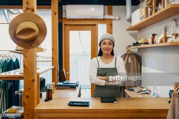 デジタルタブレット経由でモバイル決済を受け入れる準備ができている女性のスモールビジネスの所有者 - ショッピングエリア ストックフォトと画像