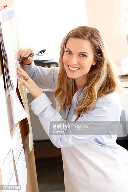 Hembra del pequeño empresario escribiendo en Calendario de pared