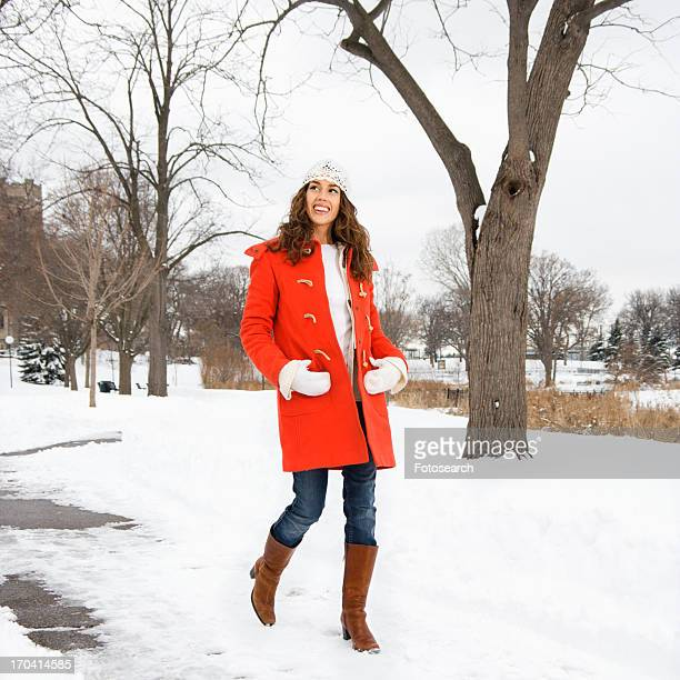 Female smiling and walking down snow covered street