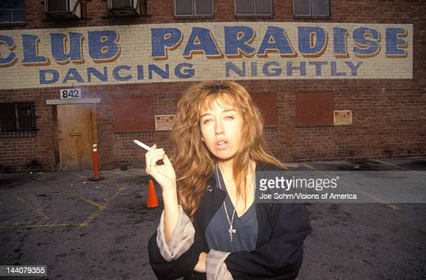 Female smoking in night club parking lot Los Angeles California