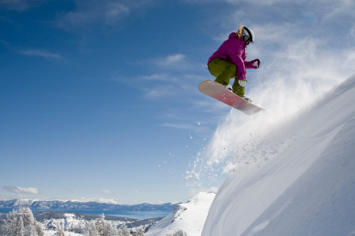 A female snowboarder doing a 540 in the backcountry on a sunny day in, California. - gettyimageskorea