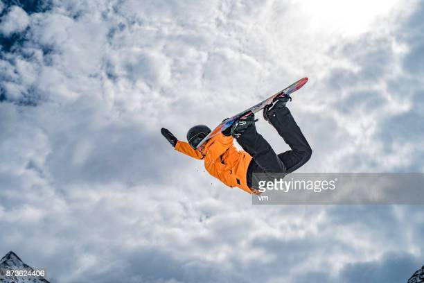 Female snowboarder doing a method grab in mid-air