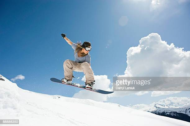 female snowboarder jumping through air - snowboarding stock pictures, royalty-free photos & images