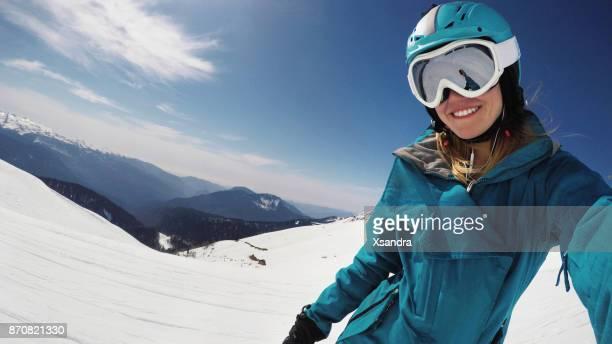Female snowboarder taking selfie