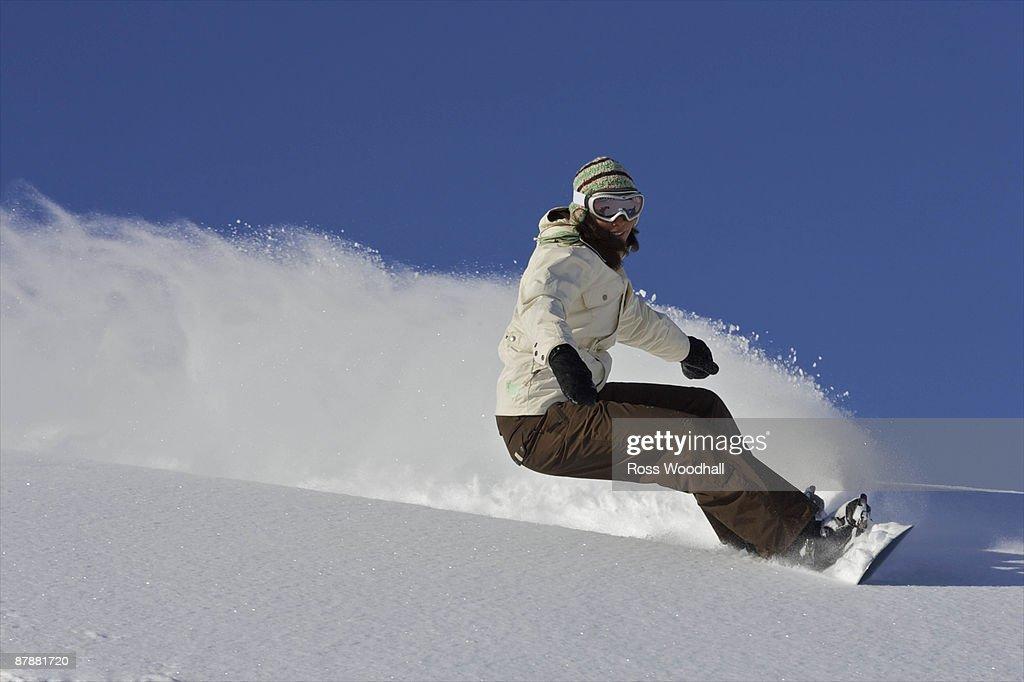 Female snowboarder turning off piste : Stock Photo