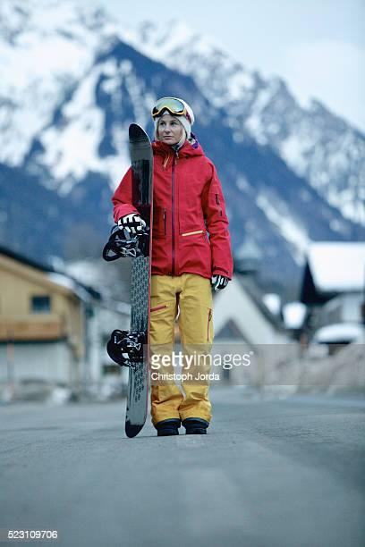 Female snowboarder walking on road, Austria