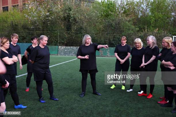 female soccer coach discussing strategy with women's soccer team on soccer pitch - menopossibilities stock pictures, royalty-free photos & images