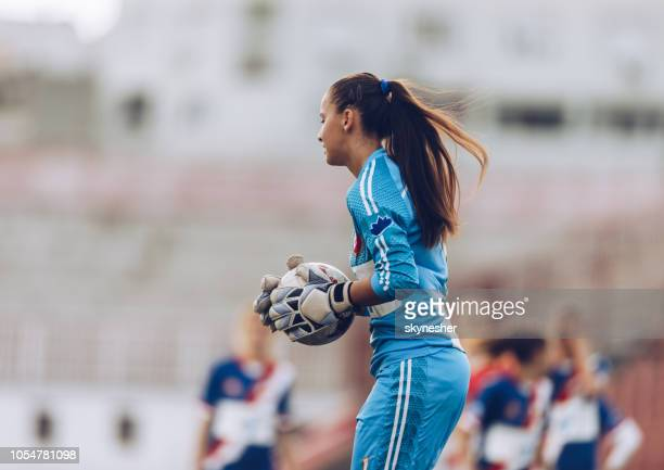 female soccer goalkeeper with a ball on a stadium. - goalie goalkeeper football soccer keeper stock pictures, royalty-free photos & images