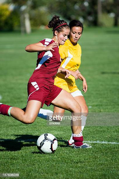 female soccer player breaks away from defender - face off sports play stock photos and pictures