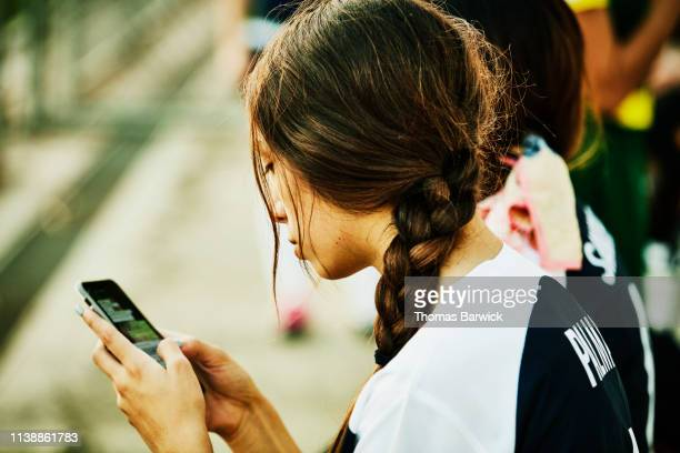 female soccer player checking smart phone after soccer match - football strip stock pictures, royalty-free photos & images