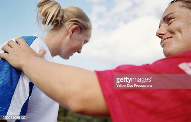 Female soccer player congratulating member of opposing team