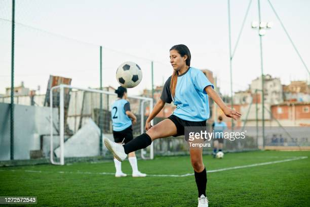 a female soccer player controlling a ball at a training. - soccer competition stock pictures, royalty-free photos & images