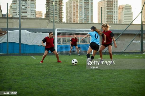 vrouwelijke voetballer die een tegenstanderverdediger dribbelt. - verdediger voetballer stockfoto's en -beelden