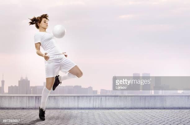 Weibliche Fußball-Spieler zu den ball an die Brust
