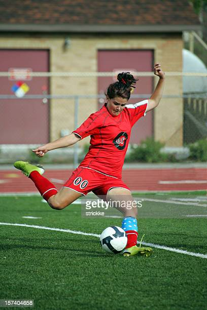 Female Soccer Player in Red Power Kicks Scoring Strike