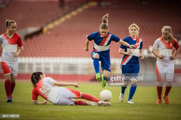 スタジアムでの試合中に相手を飛び越えて女子サッカー選手。 - tackling ストックフォトと画像