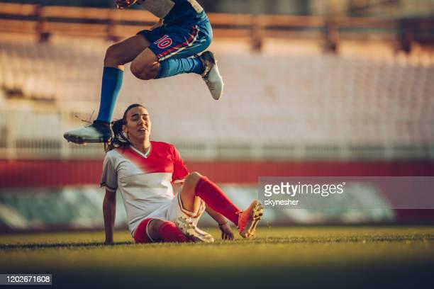 kvinnlig fotbollsspelare hoppar över motståndare under fotbollsmatch på en stadion. - anfallsspelare fotboll bildbanksfoton och bilder