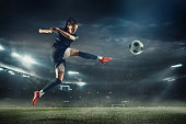 Female soccer player kicking ball at the stadium