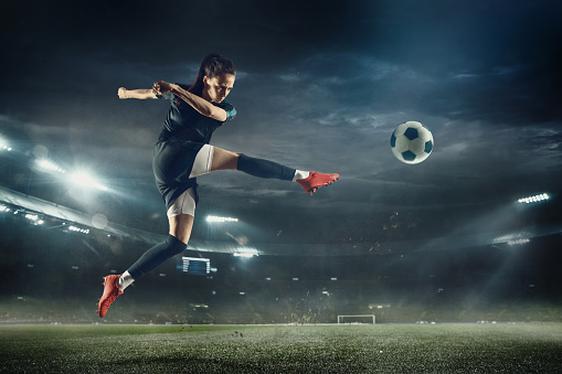 Female soccer player kicking ball at the stadium 1149530632
