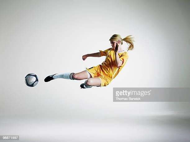 female soccer player kicking ball in mid air  - kicking stock pictures, royalty-free photos & images