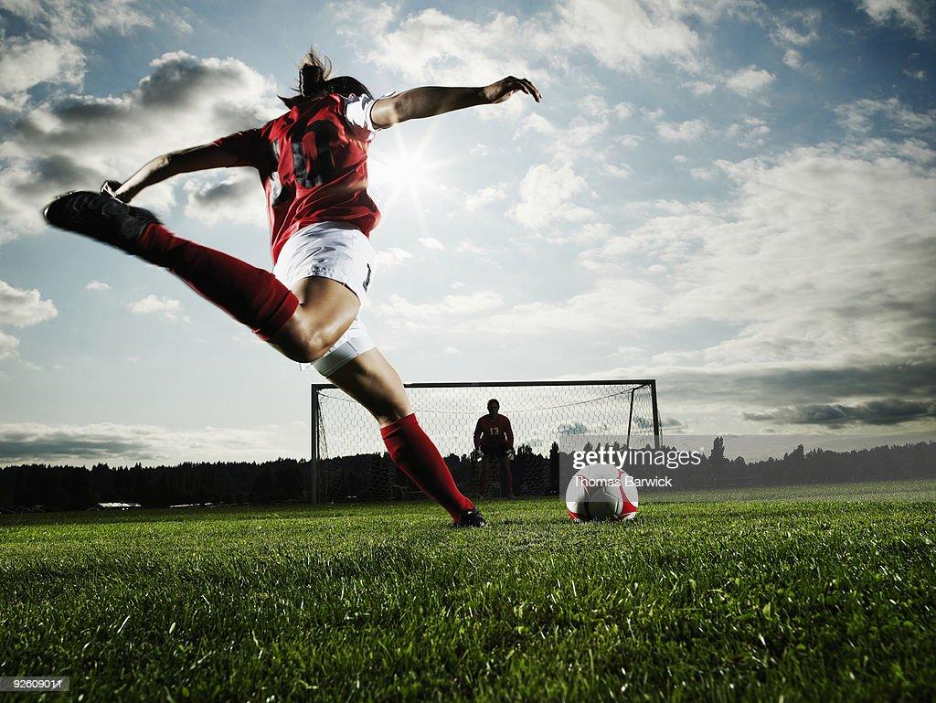 Female soccer player kicking ball toward goal : Stock Photo