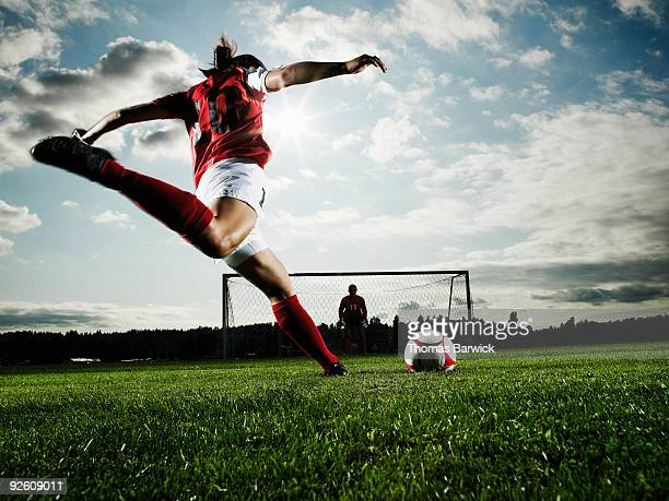 female soccer player kicking ball toward goal - portiere posizione sportiva foto e immagini stock