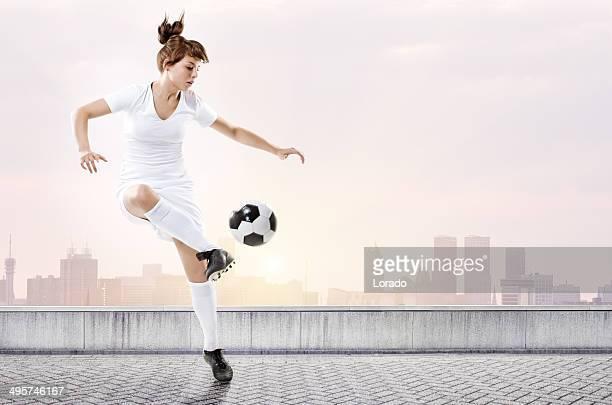 Weibliche Fußball Spieler treten den ball